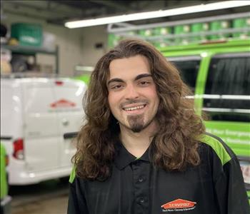 Male with long brown hair in front of SERVPRO vehicles