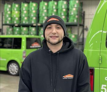 Male standing in front of SERVPRO vehicles