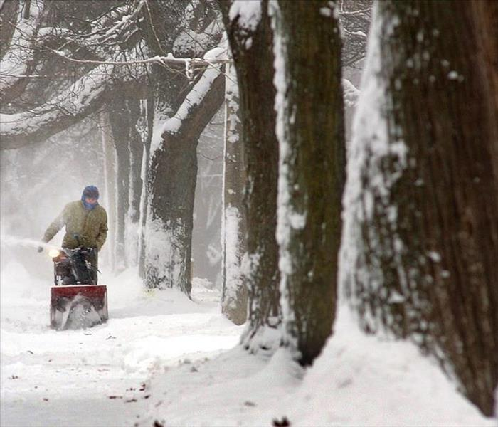 man with snowblower during blizzard